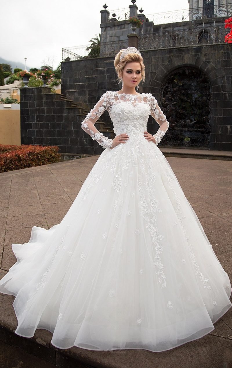 Закрытое свадебное платье пышного кроя с эксцентричным фактурным верхом с рукавом.