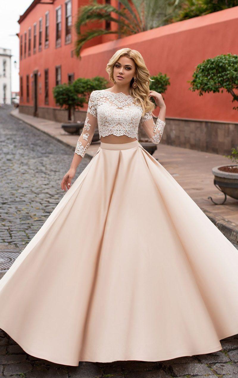 Свадебное платье с кремовой юбкой из атласа и укороченным кружевным топом с длинным рукавом.