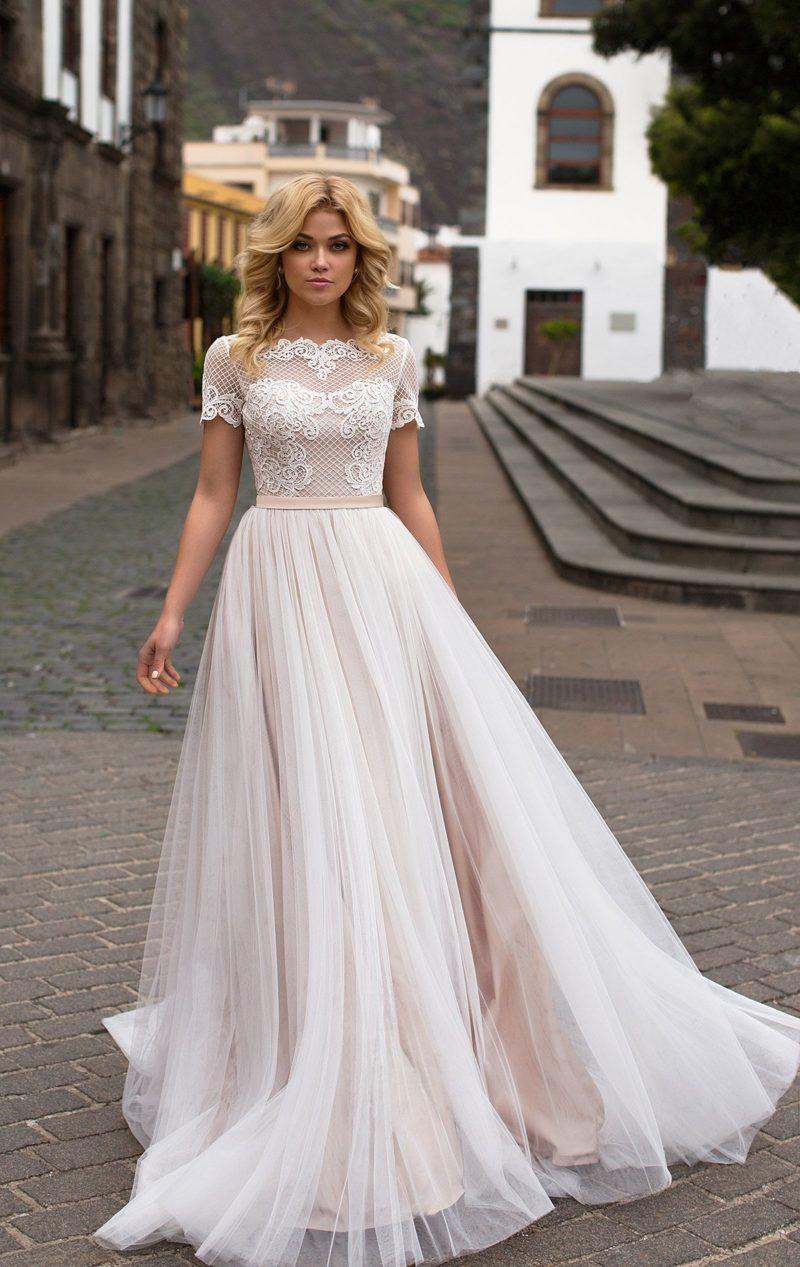 Свадебное платье с розовой юбкой под белым фатином и закрытым лифом из кружевной ткани.