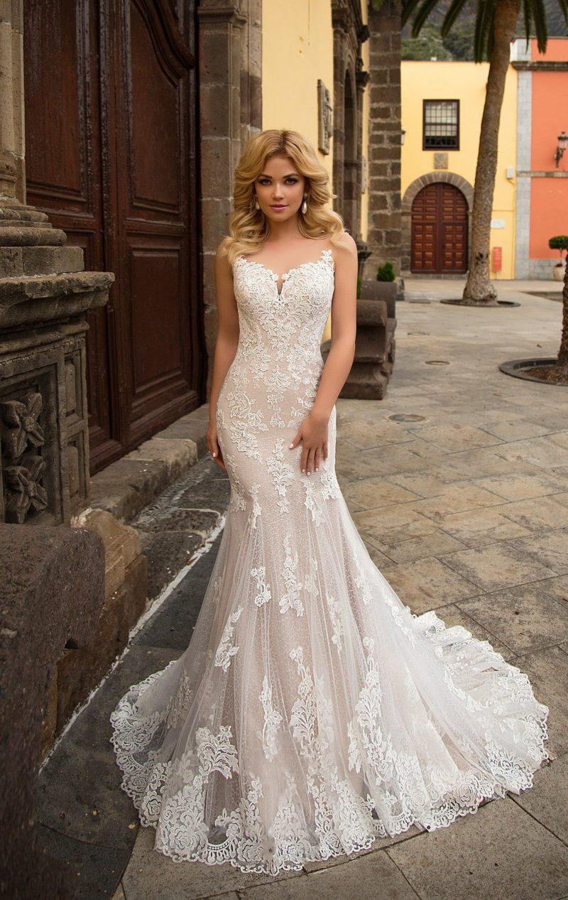 Облегающее свадебное платье на бежевой подкладке, покрытое цветочным кружевом.