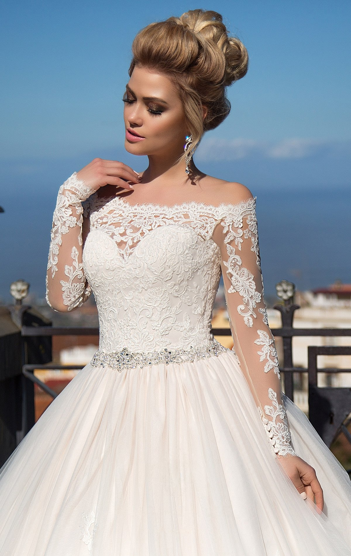 Свадебное платье с портретным декольте, длинным рукавом и многослойным пышным низом.