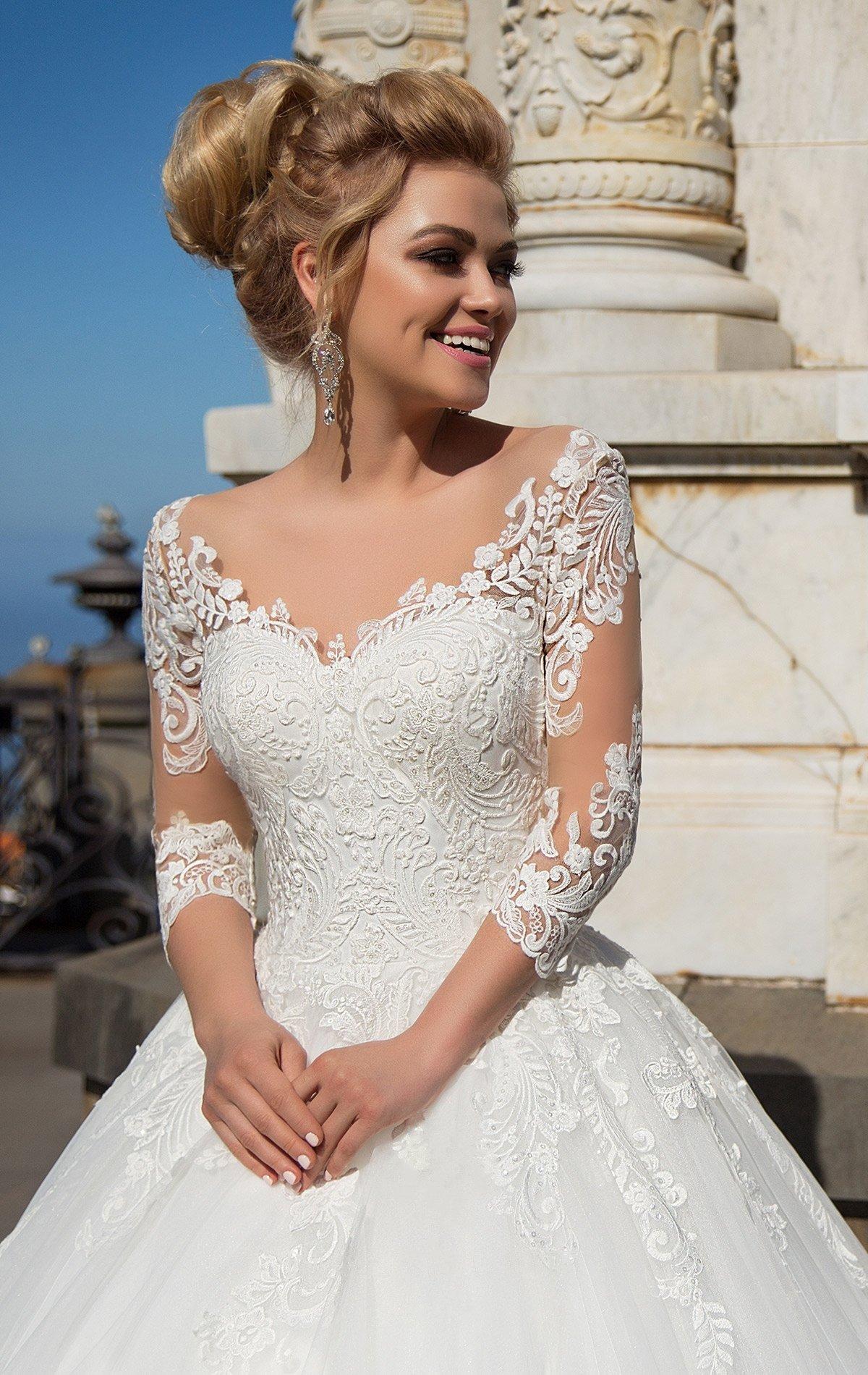 Сногсшибательное пышное свадебное платье с длинным прозрачным рукавом и элегантным вырезом.