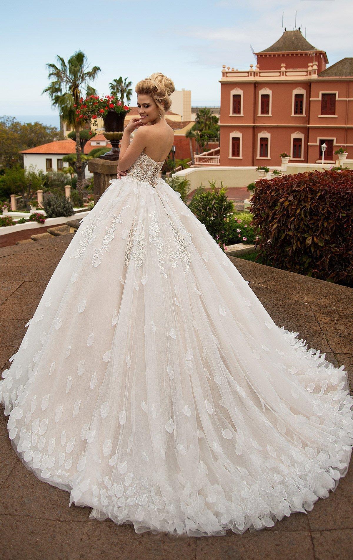 Пышное свадебное платье цвета слоновой кости с эксцентричным оформлением низа подола.