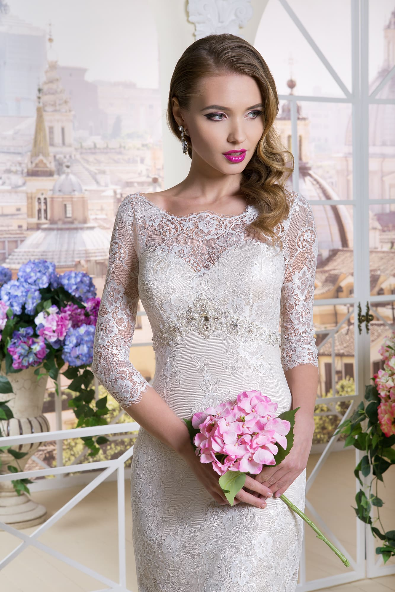 Свадебное платье-футляр длиной до колена с полупрозрачными кружевными рукавами.