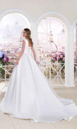 Атласное свадебное платье с лаконичным верхом с коротким рукавом и пышной юбкой со шлейфом.