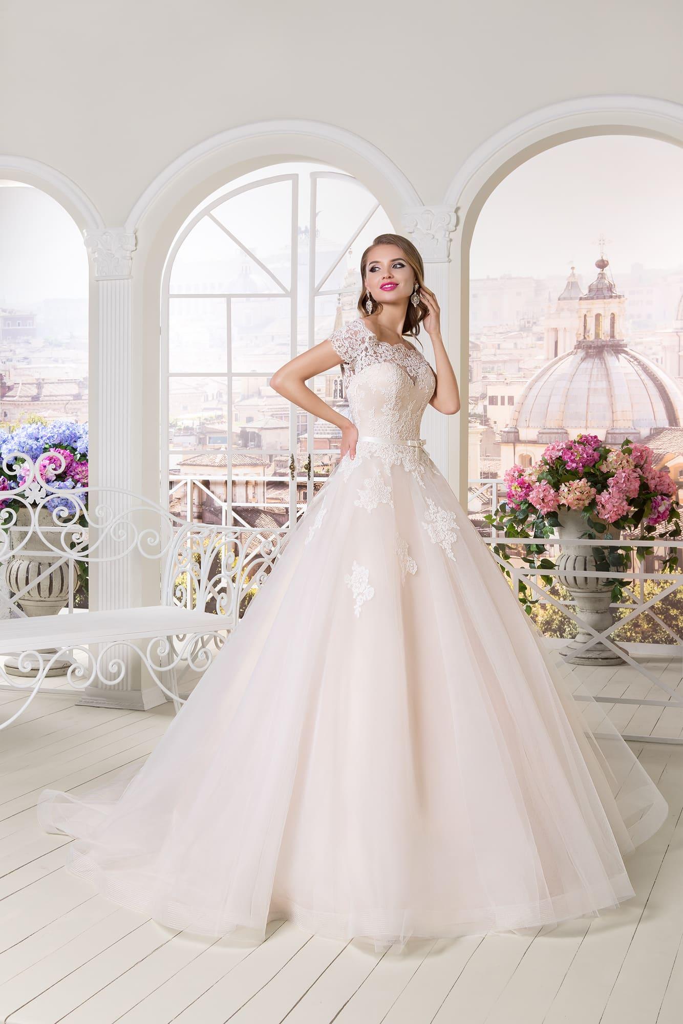 Кремовое свадебное платье с воздушной пышной юбкой и кружевными аппликациями.