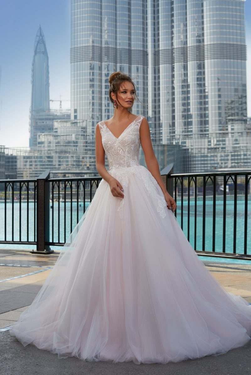Свадебное платье с воздушной многослойной юбкой и элегантным V-образным вырезом декольте.