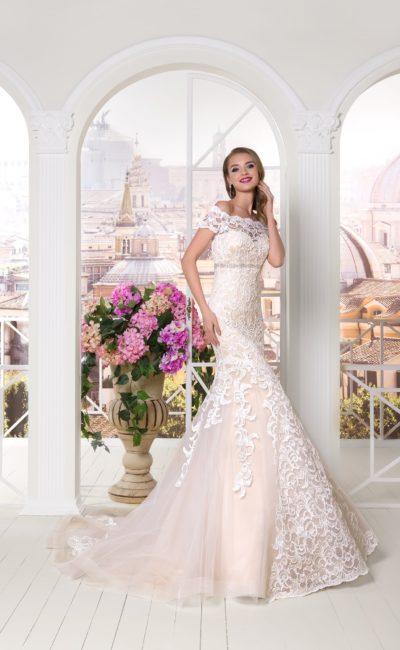Нежно-розовое свадебное платье облегающего силуэта, декорированное кружевной тканью.