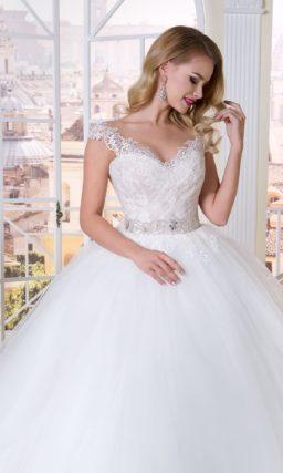 Пышное свадебное платье с небольшим ажурным вырезом и облегающим корсетом.