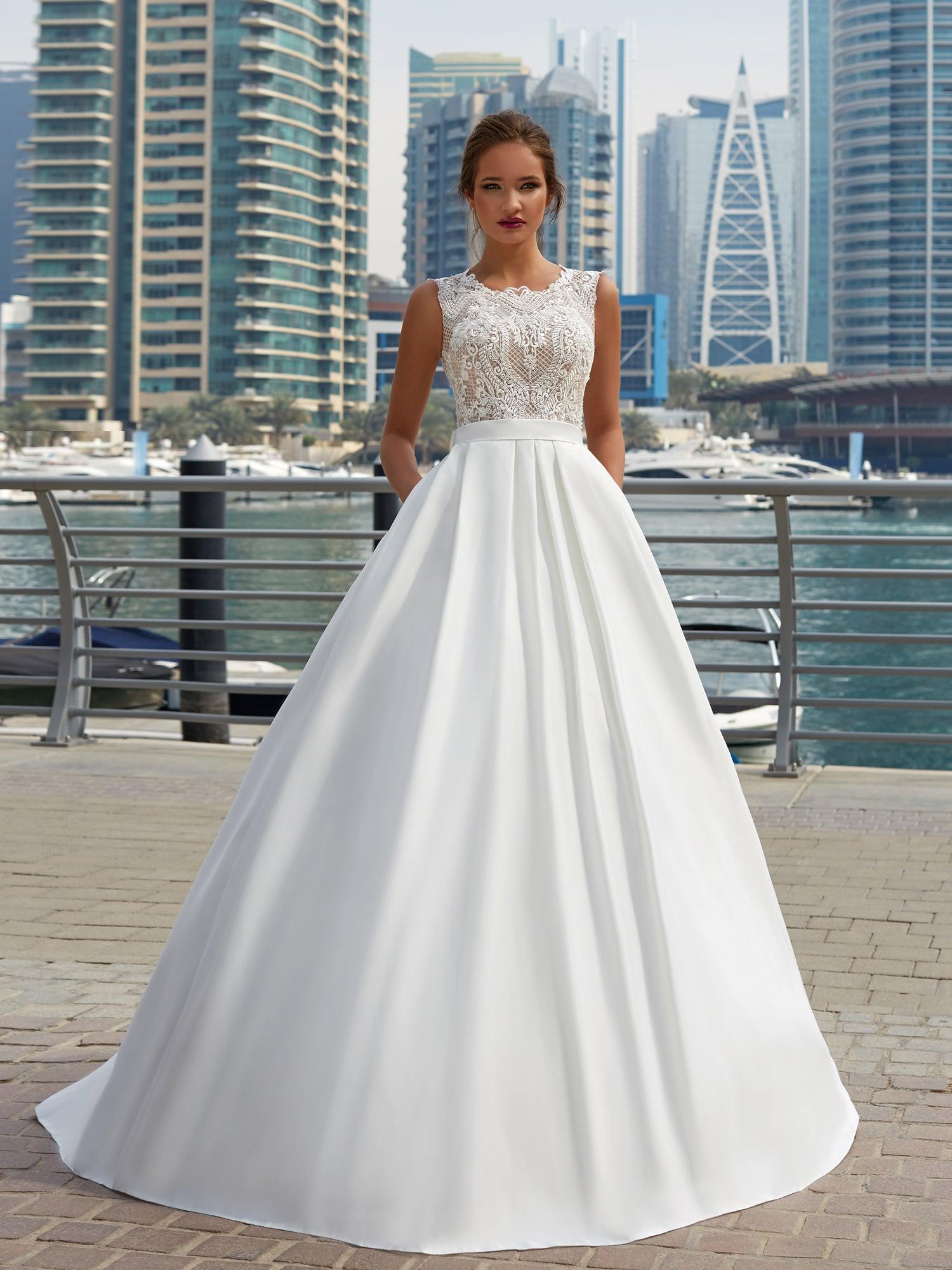 Эффектное свадебное платье с кружевным закрытым верхом и пышной юбкой со скрытыми карманами.