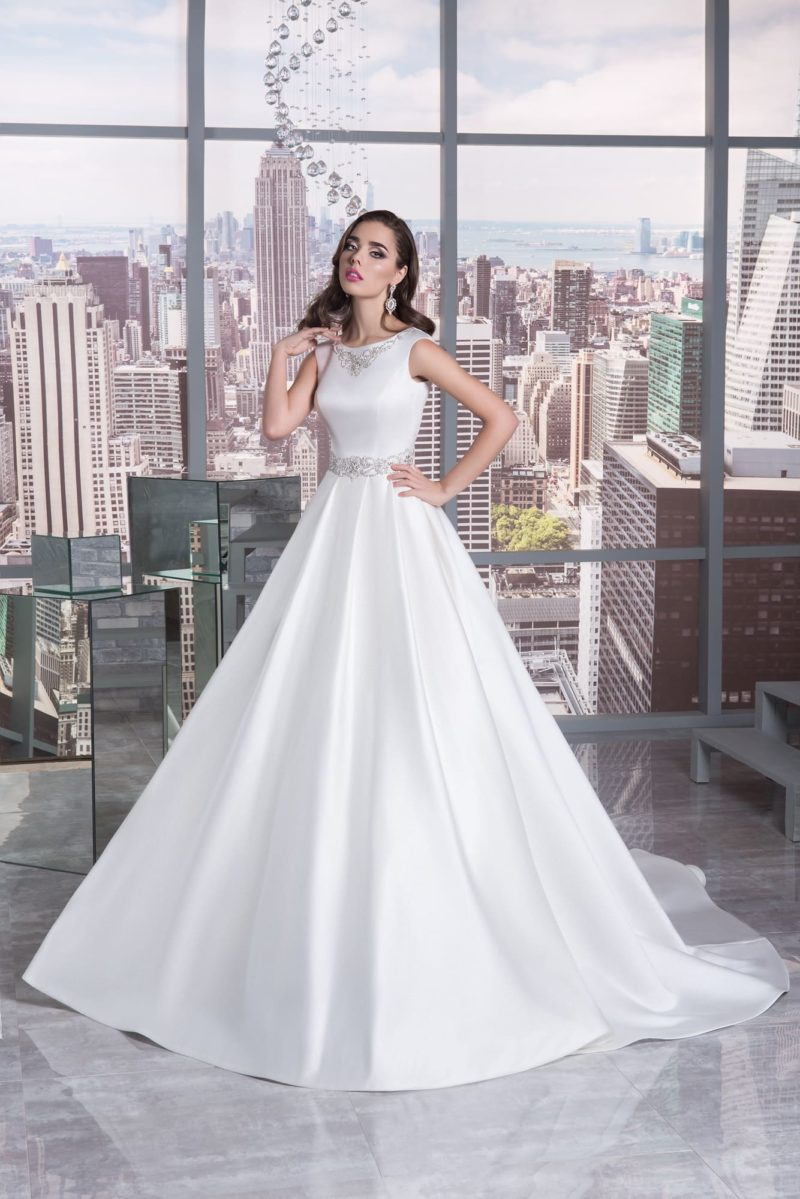 Шелковое свадебное платье А-кроя с вырезом под горло, украшенным бисерной вышивкой.