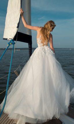 Очаровательное свадебное платье с полупрозрачным верхом и многослойным подолом.
