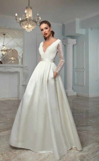 Свадебное платье с длинным кружевным рукавом и объемной атласной юбкой со скрытыми карманами.
