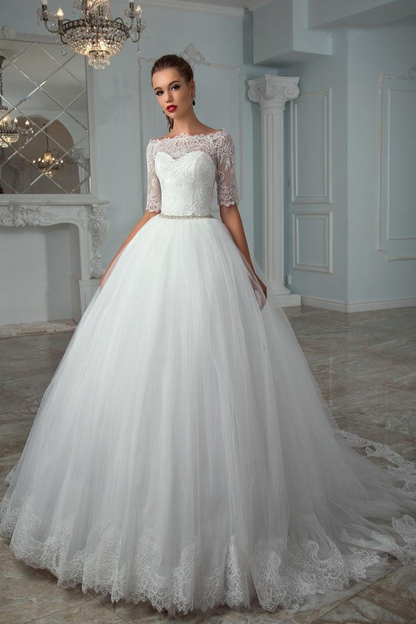 Пышное свадебное платье с портретным декольте и кружевным рукавом до локтя.