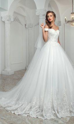 Свадебное платье с портретным декольте, кружевной отделкой и юбкой пышного кроя.