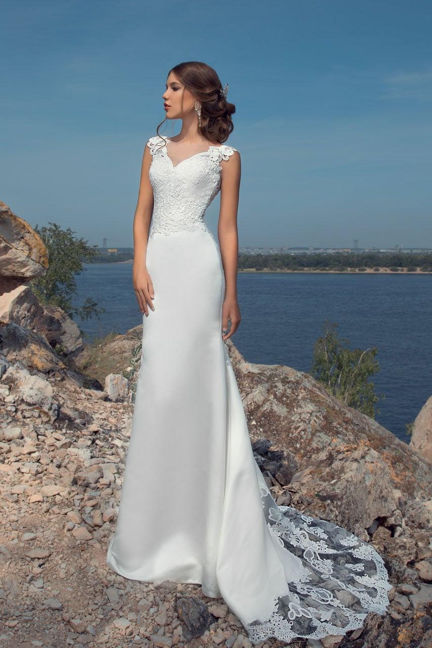 Атласное свадебное платье прямого кроя с длинным шлейфом и широкими фигурными бретелями.