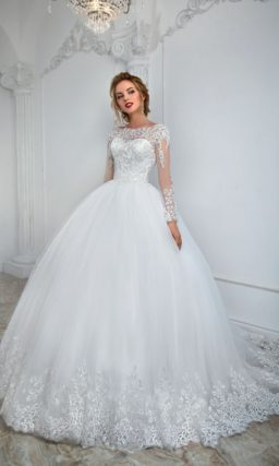 Пышное свадебное платье с округлым вырезом и длинным полупрозрачным рукавом с кружевом.