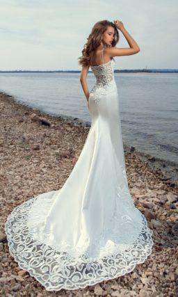 Атласное свадебное платье облегающего кроя с небольшим шлейфом и тонкой вставкой сзади.