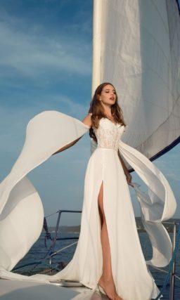 Прямое свадебное платье с разрезом на юбке и облегающим лифом из кружевной ткани.
