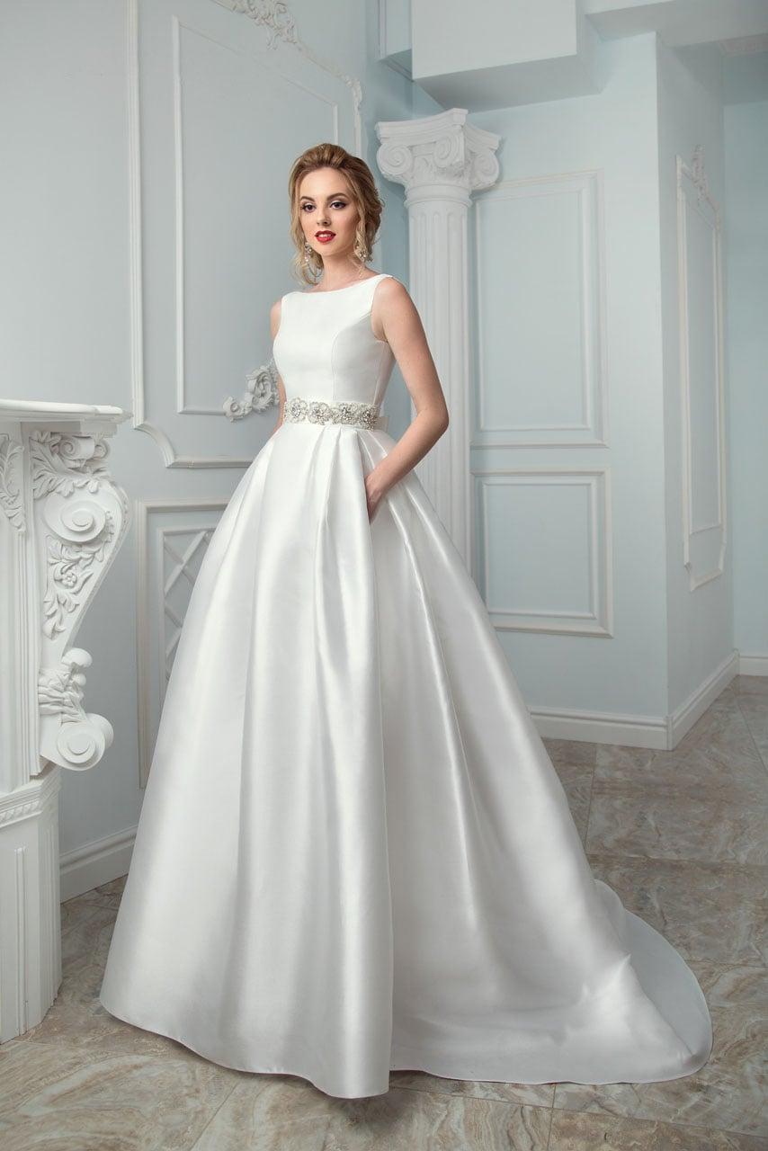 Утонченное свадебное платье «принцесса» с вырезом лодочкой и скрытыми карманами на подоле.