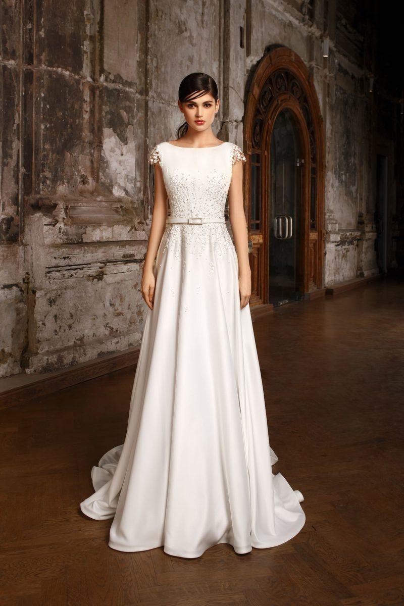 Атласное свадебное платье с вырезом «бато», украшенное бисером по рукавам и корсету.