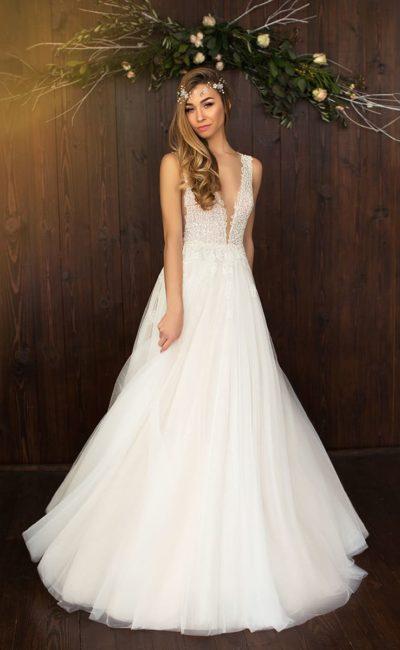 Деликатное свадебное платье с многослойной юбкой и кружевным верхом с глубоким декольте.