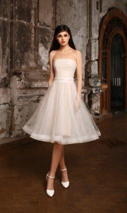 Бежевое свадебное платье с прямым лифом и многослойной юбкой А-силуэта длиной до колена.