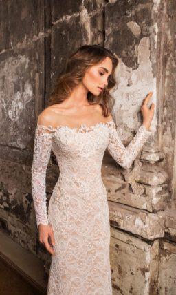 Бежевое свадебное платье с открытыми плечами и облегающим силуэтом, покрытое белым кружевом.