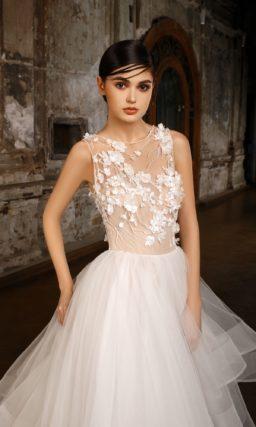 Пышное свадебное платье с многоярусной юбкой и закрытым верхом на бежевой подкладке.