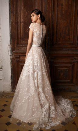Пудровое свадебное платье с закрытым лифом и юбкой «принцесса», покрытое белым кружевом.