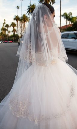 Свадебное платье с длинным прозрачным рукавом и пышной юбкой из нескольких ярусов ткани.