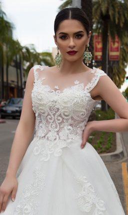 Кружевное свадебное платье пышного кроя с узкими фигурными бретелями и длинным шлейфом.
