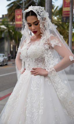 Пышное свадебное платье кремового цвета с закрытым лифом и деликатным цветочным декором.