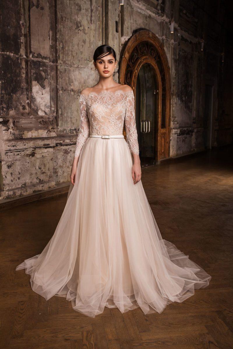 Пудровое свадебное платье с открытыми плечами, подчеркнутой талией и пышным низом.