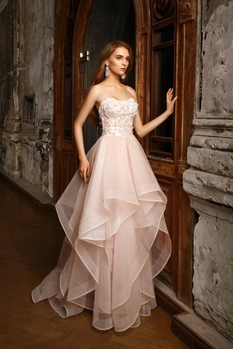 Свадебное платье с каскадами фатина по юбке и открытым корсетом с объемным декором.
