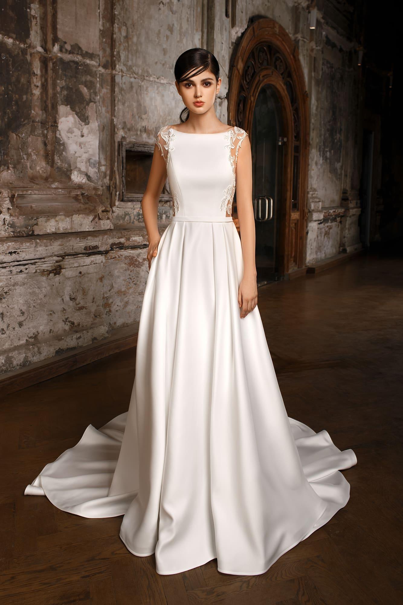 Закрытое свадебное платье из глянцевого атласа, с прозрачной спинкой и юбкой А-силуэта.