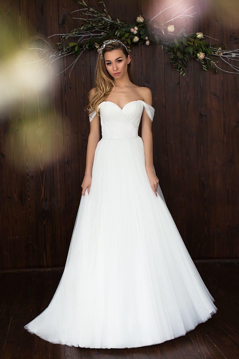 Утонченное свадебное платье А-силуэта с широкими бретелями, спущенными на предплечья.
