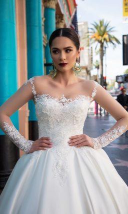 Изысканное свадебное платье с прозрачными рукавами и глянцевой юбкой с великолепным шлейфом.