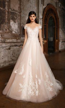Кремовое свадебное платье А-силуэта с белым кружевом по подолу и коротким фигурным рукавом.