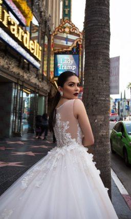 Свадебное платье с изящным верхом и пышной юбкой, украшенными кружевными аппликациями.
