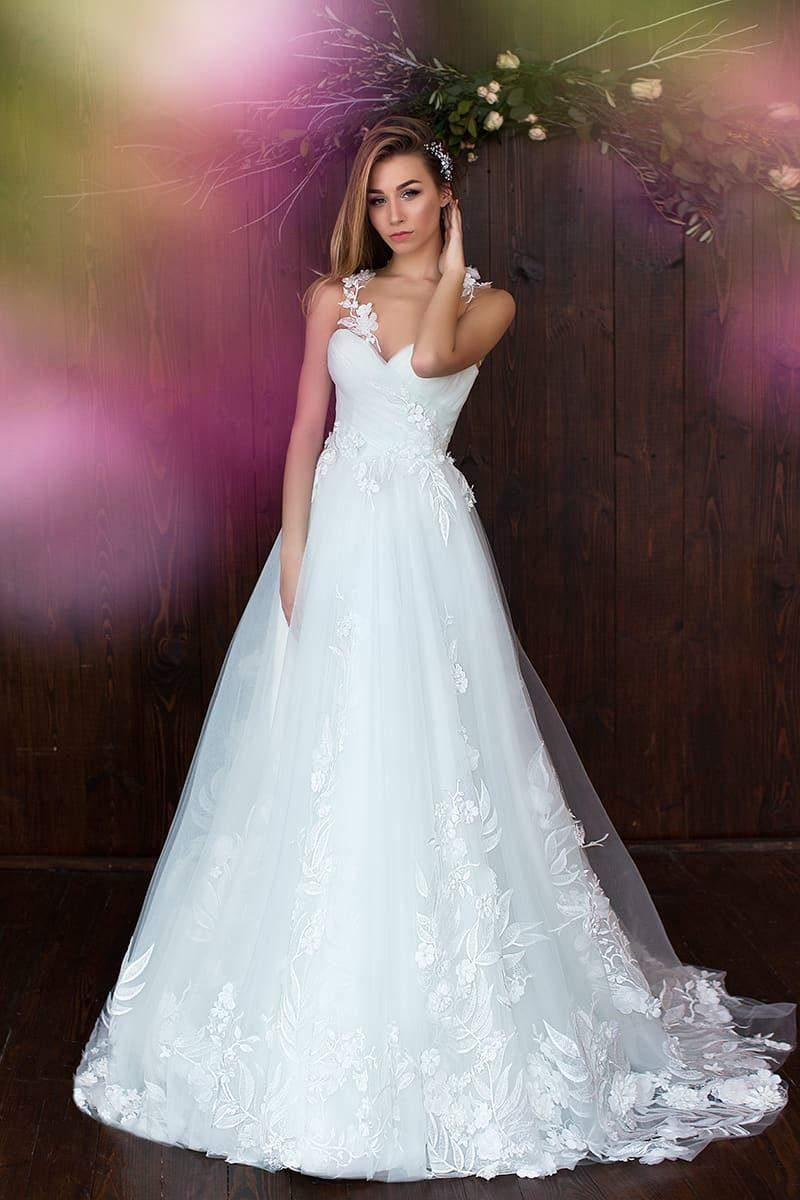 Свадебное платье пышного кроя с открытым декольте и утонченной отделкой аппликациями.