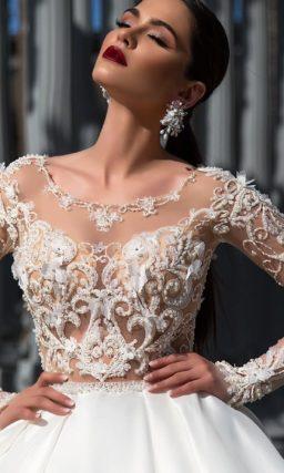 Чарующее свадебное платье с полупрозрачным верхом и пышной атласной юбкой со шлейфом.
