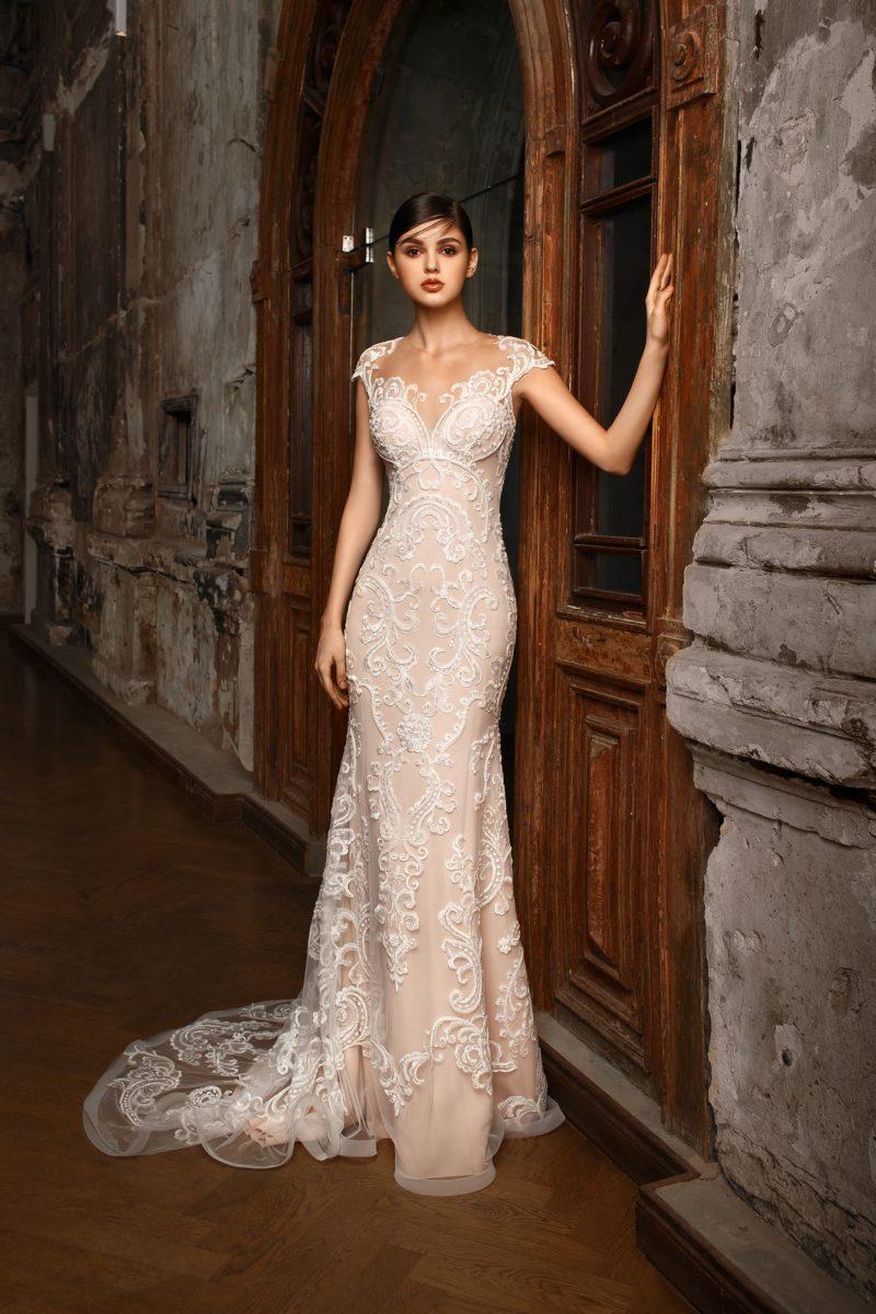 Облегающее фигуру свадебное платье на бежевой подкладке с изящным верхом и коротким рукавом.