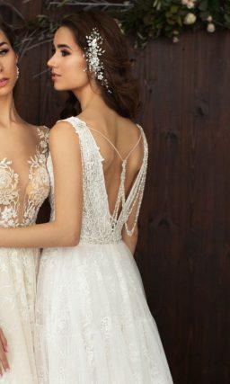 Свадебное платье цвета слоновой кости с пышной юбкой со шлейфом и нежным тонким корсетом.