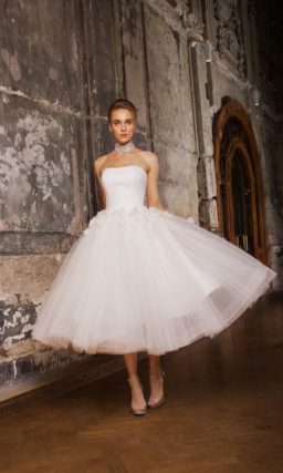 Изысканное свадебное платье пышного силуэта с короткой юбкой и объемной отделкой.