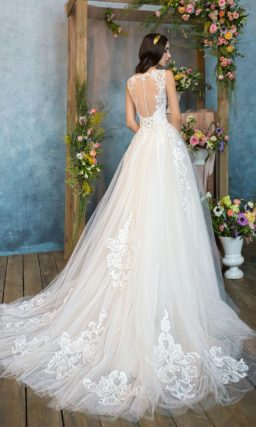 Пышное свадебное платье с легким розовым оттенком, вырезом под горло и шлейфом.