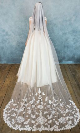 Пышное свадебное платье с роскошной кремовой юбкой, дополненной полупрозрачным верхом.