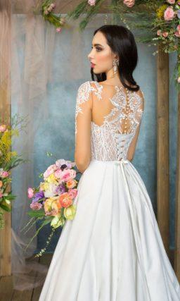 Атласное свадебное платье с роскошным шлейфом и длинным полупрозрачным рукавом с кружевом.
