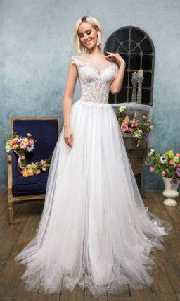 Воздушное свадебное платье с полупрозрачным кружевным верхом и фигурными бретелями.