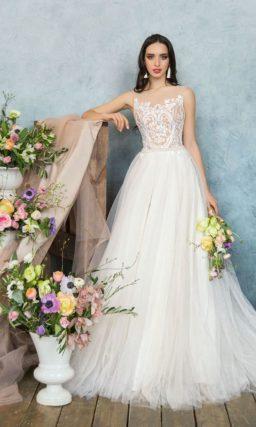 Элегантное свадебное платье с воздушной юбкой и бежевым верхом, покрытым белым кружевом.
